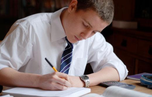 joven-con-corbata-estudiando-escribiendo-sobre-un-cuaderno